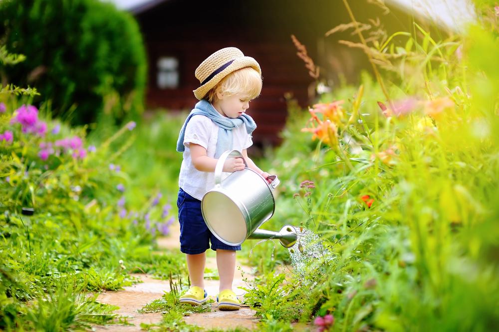 Enfant qui arrose un jardin